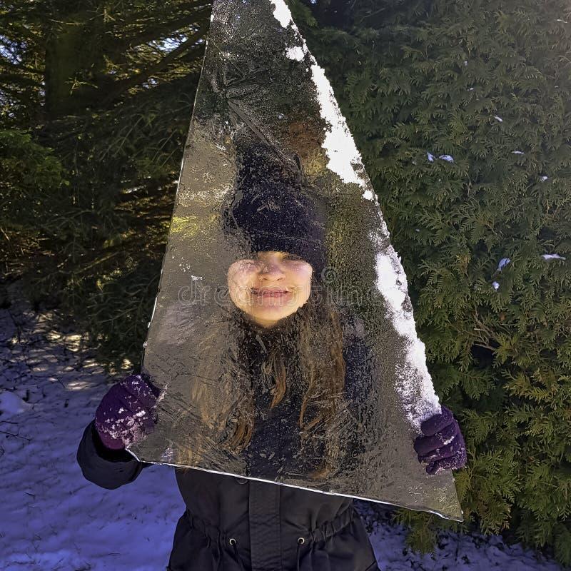 Mädchen versteckt hinter Stück Eisscholle in Choczewo, Pommern, Polen stockbild