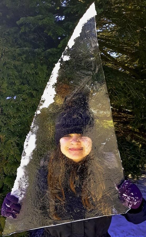 Mädchen versteckt hinter Stück Eisscholle in Choczewo, Pommern, Polen lizenzfreie stockfotografie