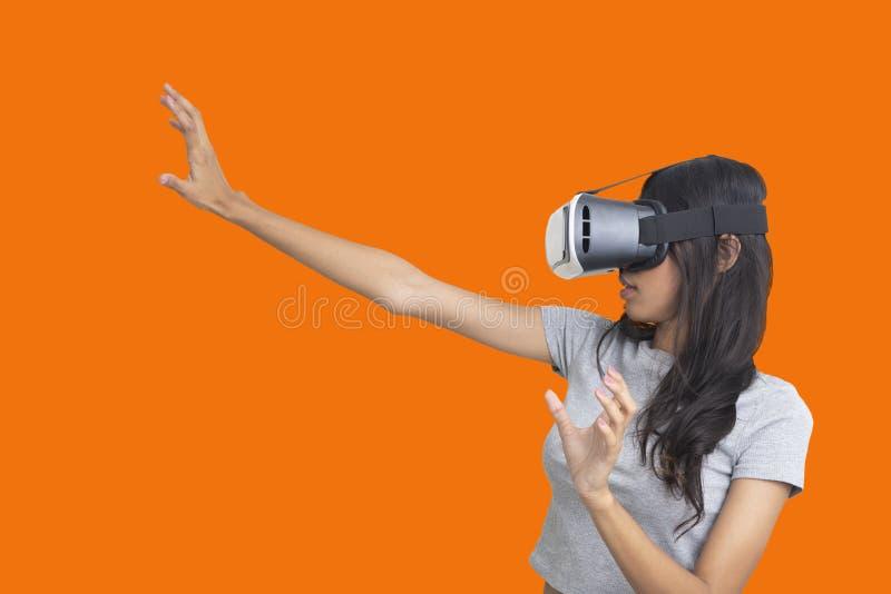 Mädchen versuchen, sometiong beim Spielen des Multimediaspiels mit Gläsern der virtuellen Realität zu fangen stockfotografie