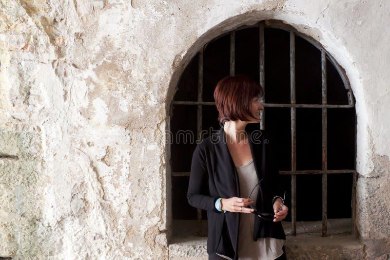Mädchen vor einem Fenster mit Stangen lizenzfreie stockfotos