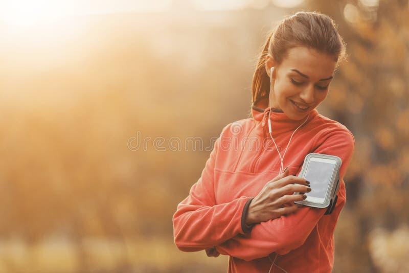 Mädchen wählen Musik für das Laufen stockfotos