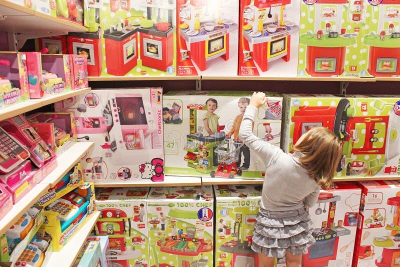 Mädchen wählt ein Spielzeug in einem Spielzeugshop lizenzfreies stockbild