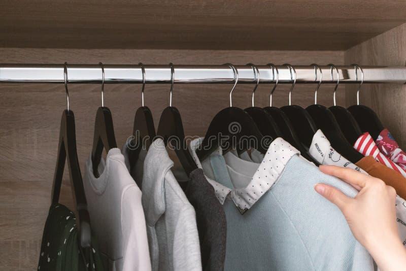 M?dchen w?hlt Kleidung f?r den Tag von der Garderobe stockfotos