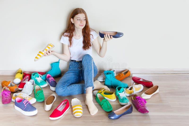 Mädchen wählt Schuhe im Zimmer auf beigem Hintergrund lizenzfreie stockfotografie