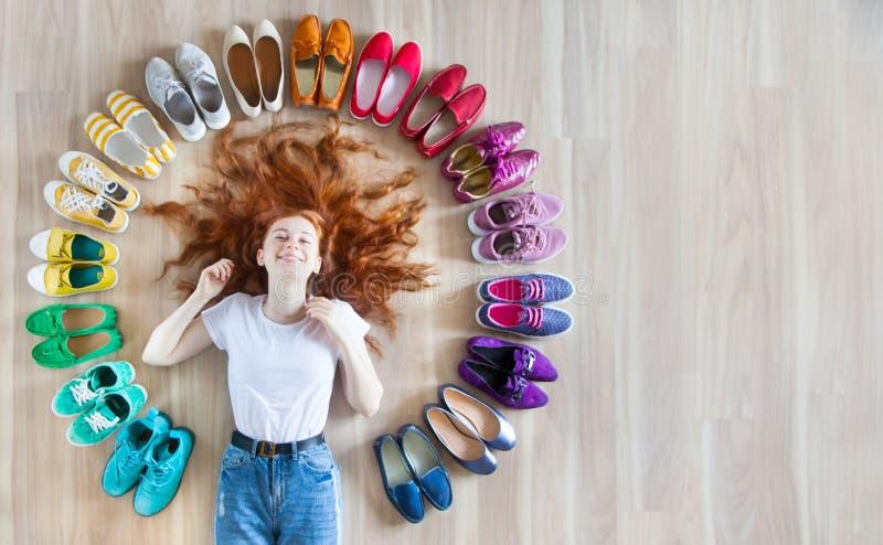 Mädchen wählt Schuhe im Zimmer auf Holzboden stockfotografie