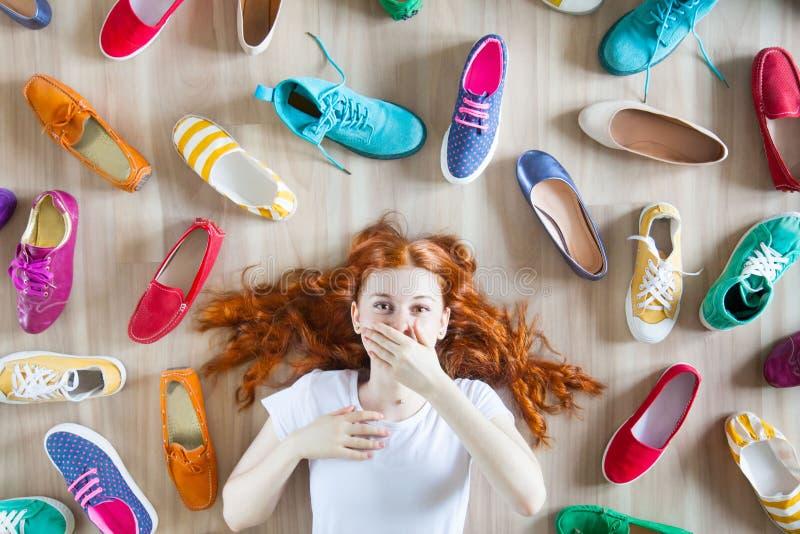Mädchen wählt Schuhe im Zimmer auf Holzboden stockfotos