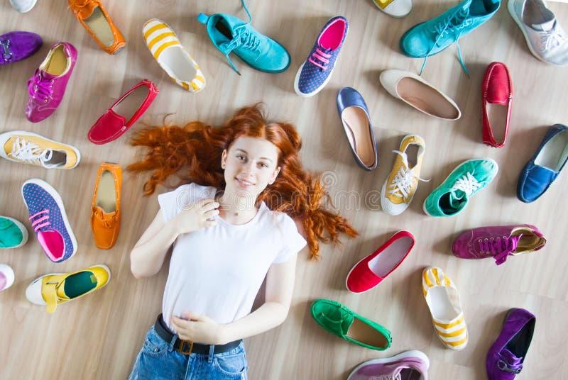 Mädchen wählt Schuhe im Zimmer auf Holzboden lizenzfreies stockfoto