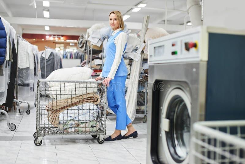 Mädchen-Wäschereiarbeitskraft rollt einen Warenkorb mit sauberem Material lizenzfreies stockfoto