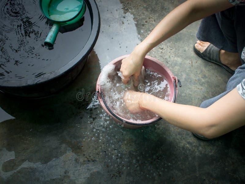 Mädchen waschen die Wäscherei neben dem Haus, um das Haus zu säubern stockbild
