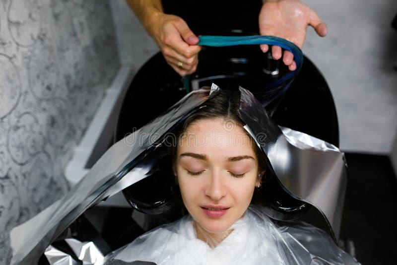 Mädchen waschen ihren Kopf in einem Schönheitssalon Haarfärbung, Folie stockbild