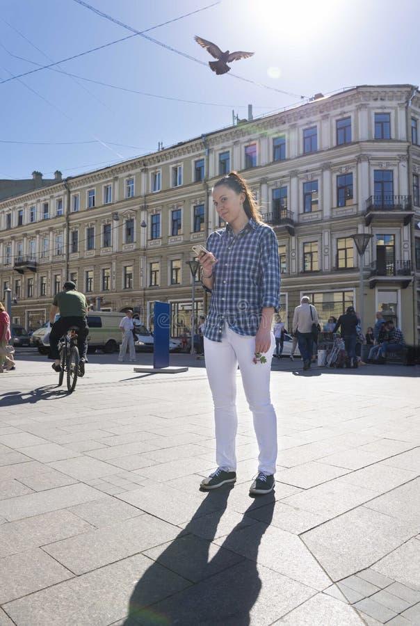 Mädchen in weißer Hose und in Hemd auf der Straße der Stadt, a tun lizenzfreies stockfoto