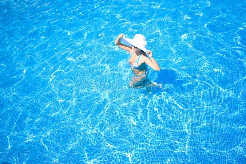 Mädchen, weißer Hut und Swimmingpool stockfotografie