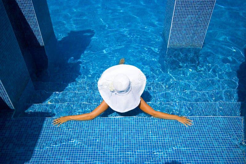 Mädchen, weißer Hut und Swimmingpool stockfoto