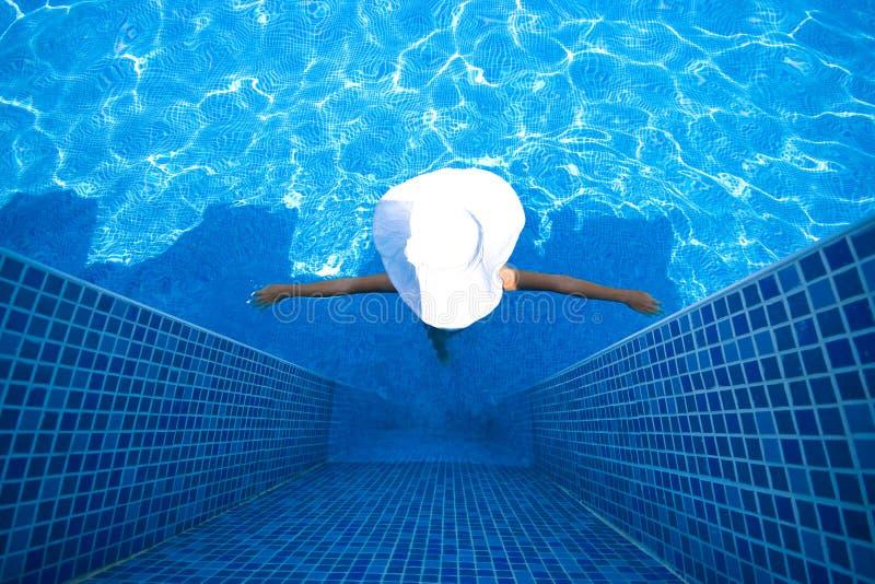 Mädchen, weißer Hut und Swimmingpool lizenzfreies stockbild