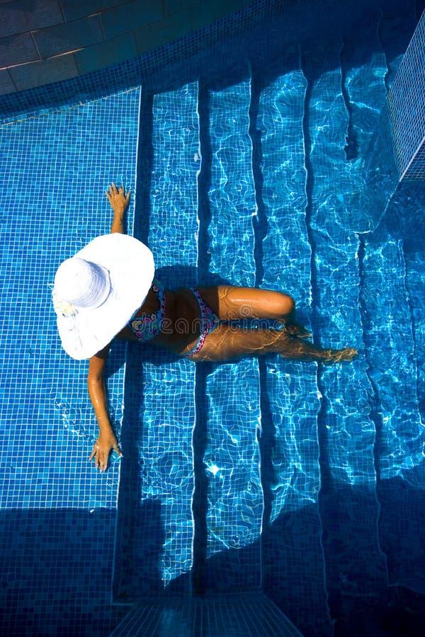 Mädchen, weißer Hut und Swimmingpool lizenzfreies stockfoto
