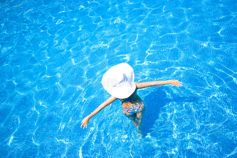 Mädchen, weißer Hut und Swimmingpool stockbild