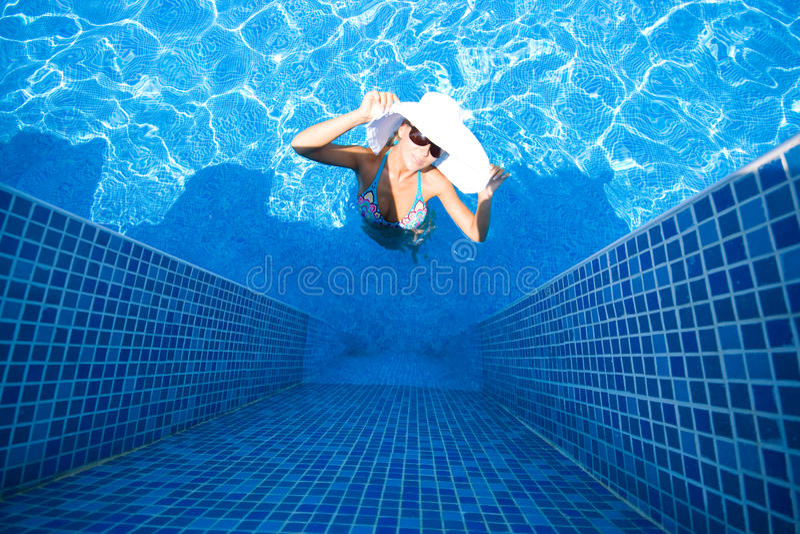 Mädchen, weißer Hut und Swimmingpool lizenzfreie stockfotos
