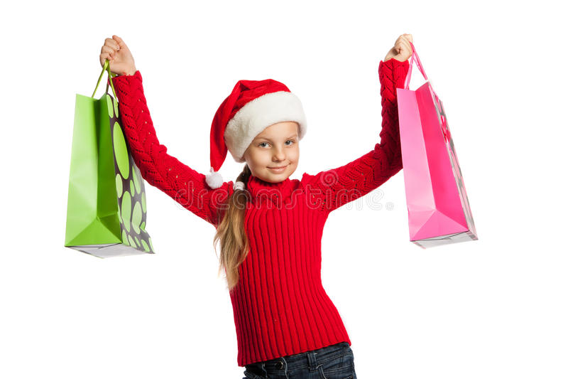Mädchen in Weihnachtsmann-Hut mit Einkaufstaschen lizenzfreies stockfoto