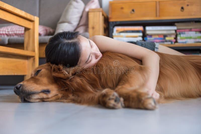Mädchen, welches das golden retriever hält, um zu schlafen stockfotografie