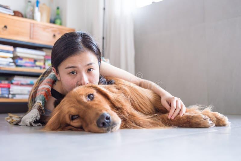 Mädchen, welches das golden retriever hält, um zu schlafen lizenzfreie stockbilder