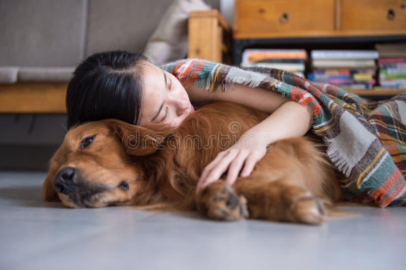Mädchen, welches das golden retriever hält, um zu schlafen lizenzfreie stockfotografie