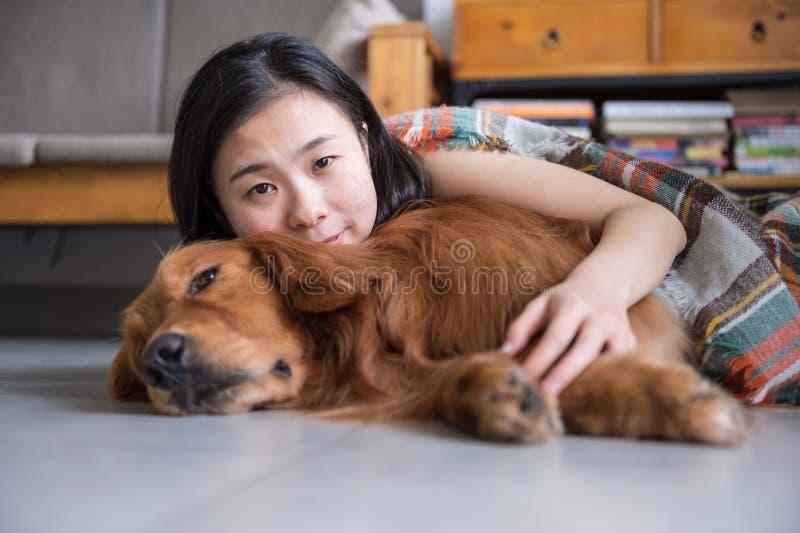 Mädchen, welches das golden retriever hält, um zu schlafen stockfotos