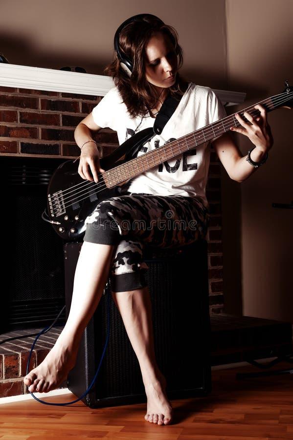 Mädchen, welches die Bass-Gitarre Innen in der Dunkelkammer spielt stockbilder