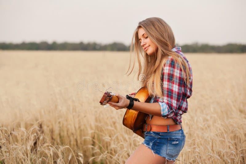 Mädchen, welches die Gitarre auf einem Weizengebiet spielt lizenzfreie stockbilder