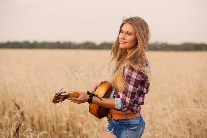 Mädchen, welches die Gitarre auf einem Weizengebiet spielt lizenzfreie stockfotos