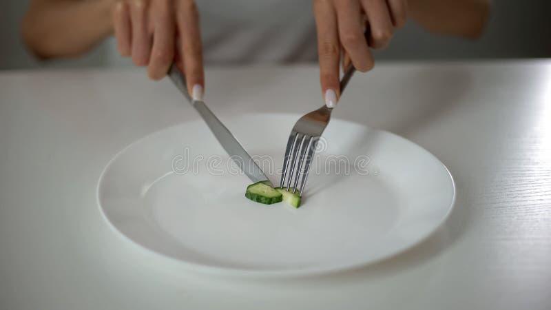 Mädchen, welches die Gurke, besessen gewesen mit dem Undereating, Furcht vor Übergewicht, Magersucht schneidet stockfotografie