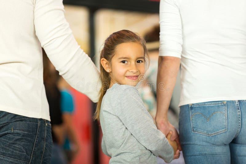Mädchen, welches die Hände des Elternteils hält stockbild