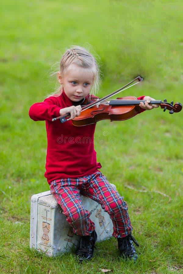 Mädchen, welches die Violine im Park spielt stockfotografie