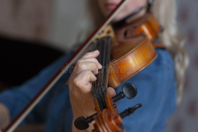 Mädchen, welches die Violine spielt Hand eines Mädchens und der Geige stockbild
