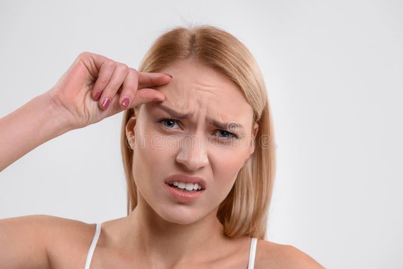 Mädchen wird mit ihrer Gesichtshaut unzufrieden gemacht lizenzfreie stockfotografie