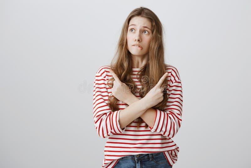 Mädchen wird verwirrt, wenn man Wahlen trifft Porträt von nervösen zweifelhaften Studentinüberfahrthänden und -c$zeigen in unters lizenzfreie stockfotos