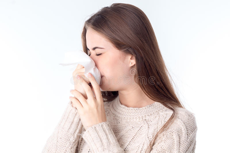 Mädchen wischt ihr Nasenhalstuch ab, das Ihre Augen schließt, wird lokalisiert auf einem weißen Hintergrund stockbilder