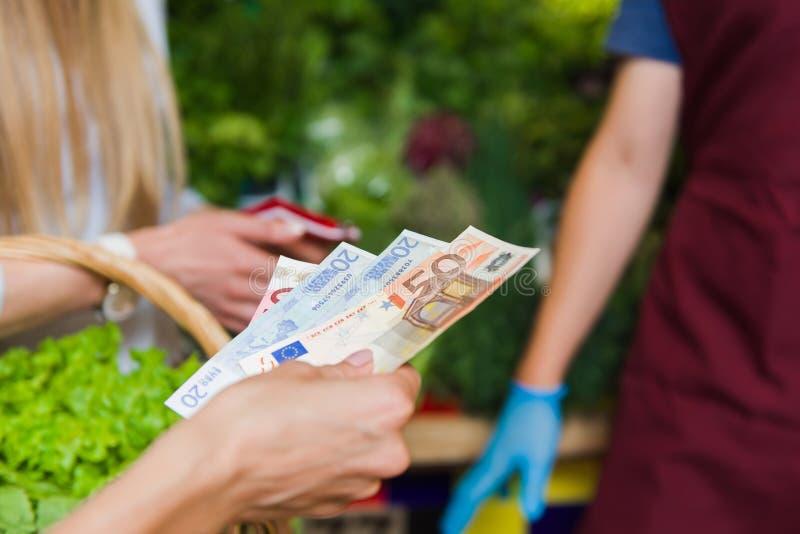 Mädchen zahlt für Bargeld auf dem Markt lizenzfreie stockfotos