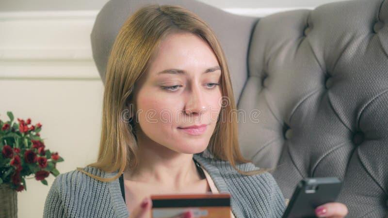 Mädchen zahlt Kauf durch Telefon stockbild