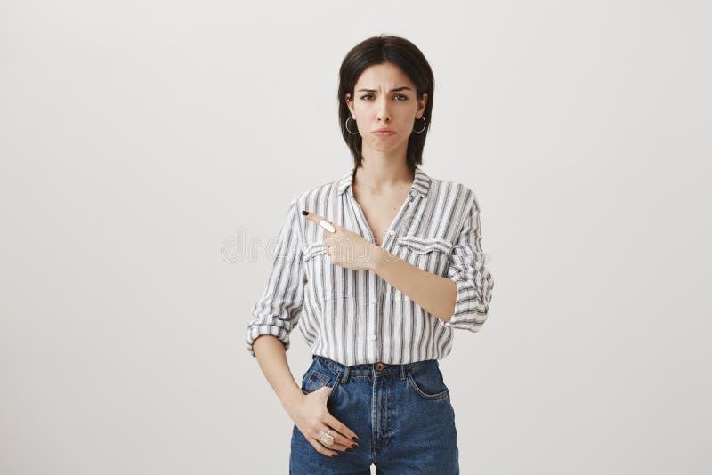 Mädchen zeigt an der Person an, die ihr wütendes und umgekippt machte Düstere enttäuschte junge Frau in der stilvollen Kleidung d lizenzfreies stockfoto