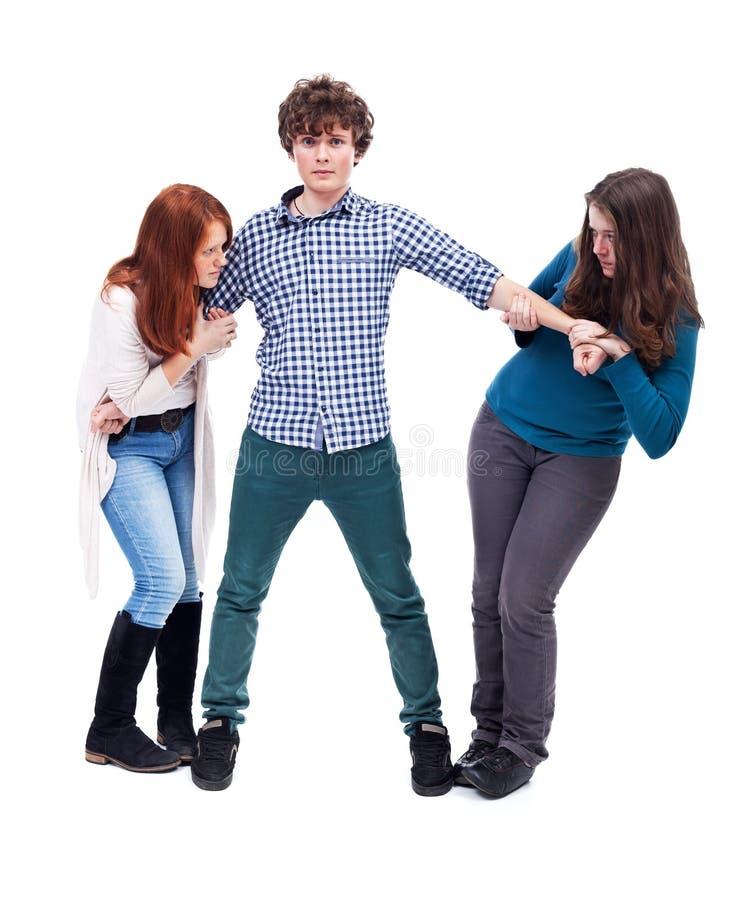 Mädchen zwei, das über einem Jungen kämpft stockbild
