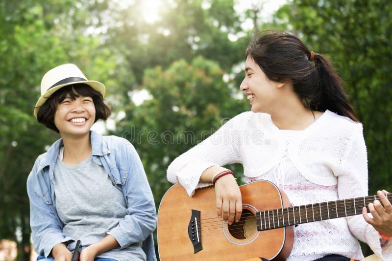 Mädchen zwei, das Gitarre und Lächeln mit glücklichem in der Natur spielt lizenzfreie stockfotos