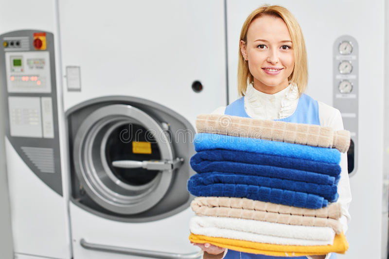 Mädchenarbeitskraft, die saubere Tücher eines Wäsche-Service hält stockfotografie