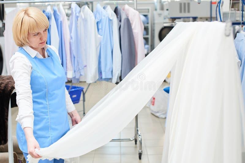 Mädchenarbeitskraft Wäscherei schaut und überprüft von weißem, bloßem Tulle lizenzfreies stockbild