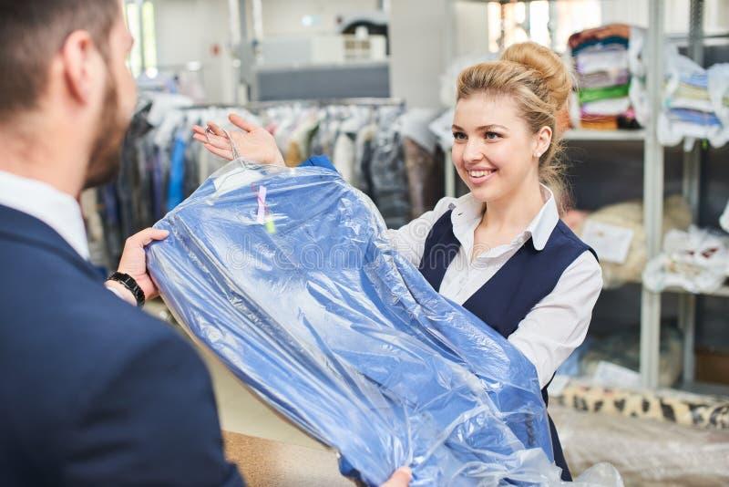 Mädchenarbeitskraft Wäschereimann gibt dem Kunden saubere Kleidung lizenzfreie stockfotografie