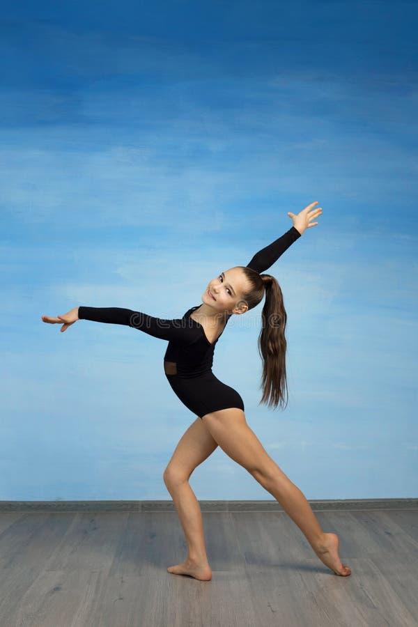 Mädchenathlet, der die Übungsgymnastik, die Kamera auf einem blauen Hintergrund betrachtend tut stockfotografie