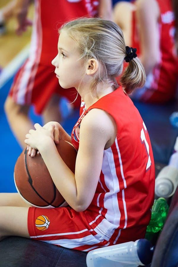 Mädchenathlet mit dem Basketball, der auf Bank sitzt lizenzfreie stockbilder