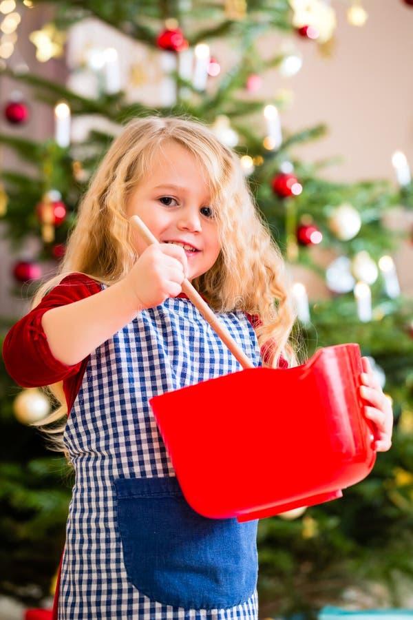 Mädchenbackenplätzchen vor Weihnachtsbaum stockfoto
