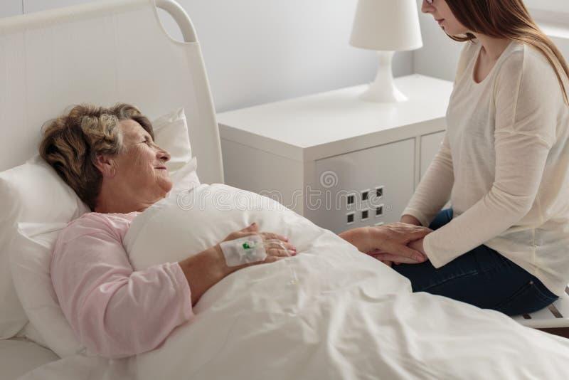 Mädchenbesuchsgroßmutter am Krankenhaus stockfotografie