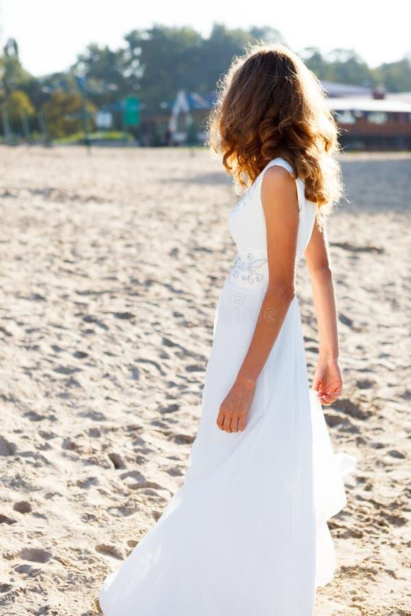 Mädchenbraut in einem weißen Kleid auf dem sonnigen Strand drehte sich zu uns lizenzfreie stockfotos