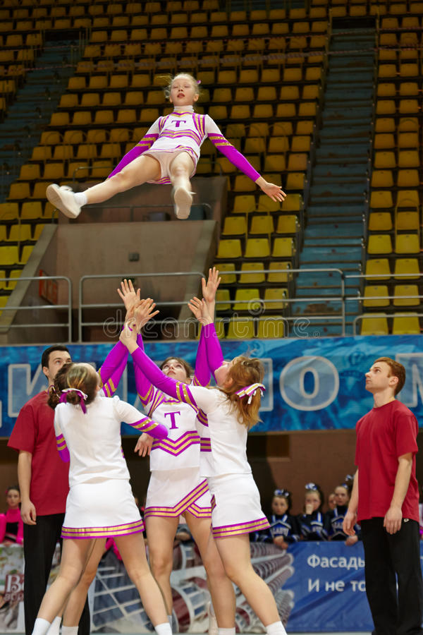 Mädchencheerleaderteam führt Akrobatik durch lizenzfreie stockbilder